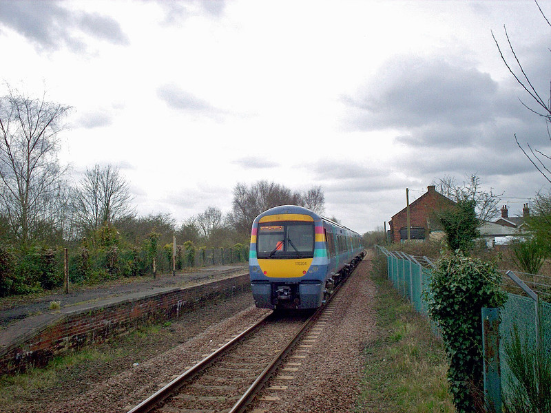 "Turbostar 170204 in ""one"" livery arrives at Wickham Market with the 0938 Liverpool Street to Lowestoft  service on 2nd April 2008. The abandoned Up platform is to the left."