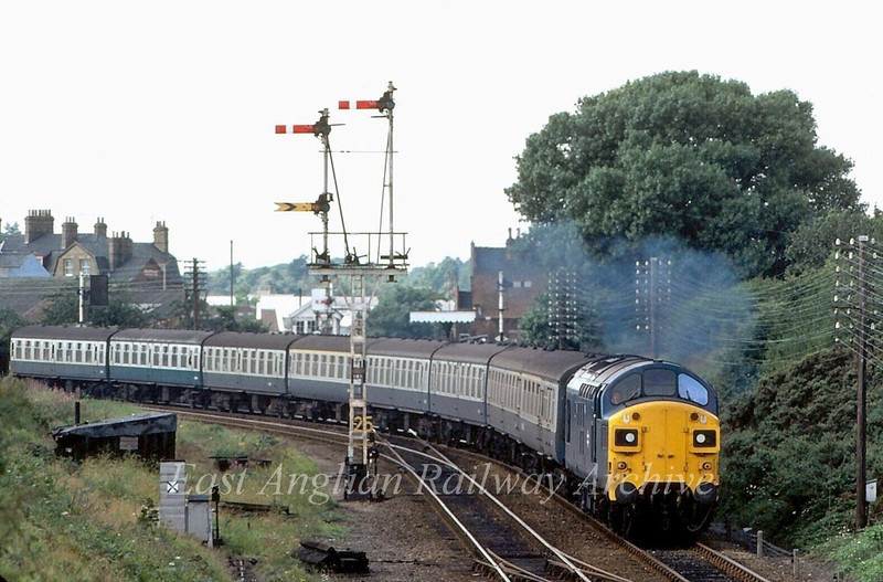 37049 heads onto the home straight at Oulton Broad Junction with the 0952 Summer Saturdays only Liverpool Street to Lowestoft. Taken with a 200mm lens from the bridge at Normanston Park. Think I was lucky to get the last carriage in the shot. Oulton Broad North station is in the background.  30th August 1980.