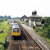 View from Wickham Market Bridge on 28th June 1979. The 1048 Lowestoft to Ipswich is arriving at the now abandoned Up platform. The disused goods shed can be seen in the background.