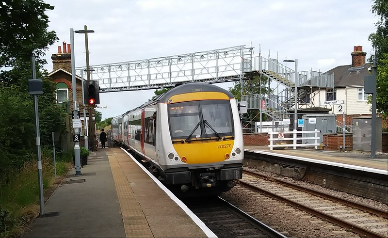 Turbostar, 170270 stands at Westerfield on 2nd July 2019. In the background a temporary footbridge has been erected to enable pedestrians to cross the line. The B1077 road has been closed while Network Rail carry out work on the barriers, conversion of AHB to full barriers. To the left is signal CO206. A once familiar unit across the area, 170270 has now been transferred to Cardiff Canton depot.