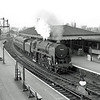"A fine shot of Beccles c1958 with Britannia Pacific 70034 ""Thomas Hardy"" arriving on a Yarmouth South Town to Liverpool Street working. Beccles North Junction signal box can be seen to the left. The junction split signals can be seen at the end of the platform. To the left, the Waveney Valley Line. The centre, Yarmouth South Town and the right to Lowestoft. Image:- J.S. Doubleday."