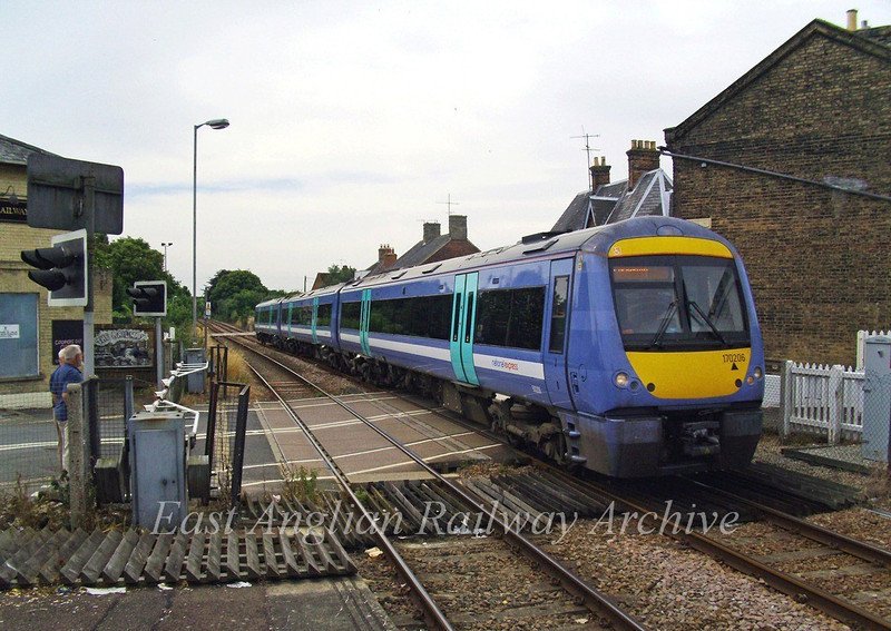 Turbostar 170206 in NXEA livery eases over Albion Street level crossing at Saxmundham with a Liverpool Street to Lowestoft working on 17th June 2009.