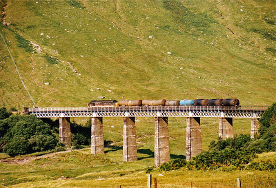 37401 passes over Auch Gleann Viaduct with its mixed rake of tanks.  I am unsure of what the third and fourth tanks could be for.  3/9/1991
