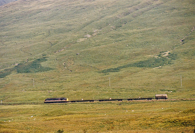 /An unidentified InterCity liveried class 37 heads towards Bridge of Orchy with a Mossend to Fort William freight comprising of 3 bogie bolsters and a solitary tank wagon.  2/9/1991