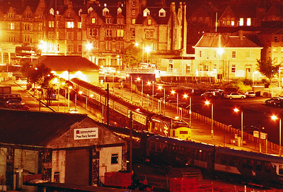"An overnight stop was had in Oban and looking down on the station is 37403 and a rake of six mkI and mkII coaches.  This worked in with the 1820 off Glasgow Queen Street.  Another class 37 is trying to hide in the other platform road.  In the right foreground is class 104 DMU 53434, 53424 in its unique maroon and white livery, it was known as the ""Mexican Bean""!  13/8/1987"