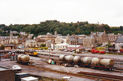 InterCity liveried 37404 is coupled to a short rake of two oil tanks in Oban station.  Three more tanks are in an adjacent siding.  This traffic is long lost to rail.  19/8/1990