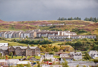 A dark sky contrasts with the bright sun on the houses of North Oban as the train descends from the summit at Glencuitten Crossing at 301 feet to sea level at the station in just three miles.
