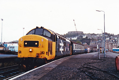The next morning and 37403 is ticking over and waiting for its 0800 departure back to Glasgow Queen Street.  McCaig's Folly stands on the hillside watching over Oban.  14/8/1987