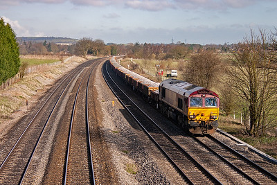 An engineers working rumbles by on the up relief with 66056 hauling a lengthy rake of 40 MHA and MTA wagons loaded with ballast.