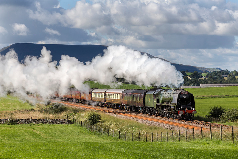 With the legendary Pendle hill dominating the background, 46233 Duchess of Sutherland climbs past Paythorne on 5th August 2017.   The strong westerly breeze nearly spoiling the shot