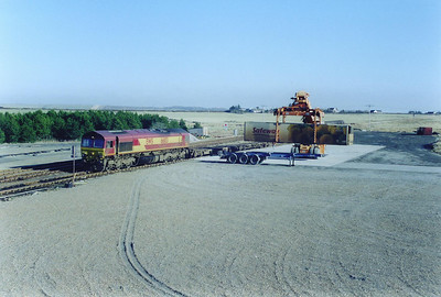 The train stands beside the hardstanding used for loading and unloading. The box is being unloaded by the reach stacker.