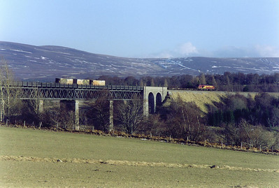 The line is carried high over the River Findhorn by the impressive Findhorn Viaduct on the 1 in 60 climb to Slochd Summit.    The rear of the train is on the viaduct but 67016 is well clear.  Time to drive home and thaw out.  The wind chill was well below zero.  19/2/2003