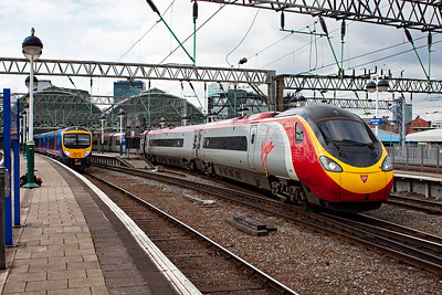A pair of departures from Piccadilly station get away. On the right is Pendolino 390031 with 1A46 1455 off, and on the left is 185146 with 1P1328 York to Manchester Airport. This unit arrived a short time earlier and reverses here to head for the airport.