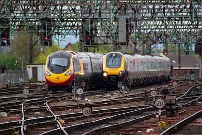 Virgin Pendolino 390043 departs with 1A44 1435 off to Euston and it passes former Virgin Voyager 221124 with 1M38 0945 from Bournemouth which will terminate here.