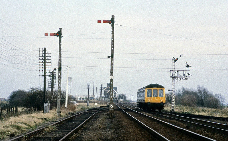 French Drove, facing March showing the Up and Down goods loop split signals. The Up loop exit signal is to the extreme left. The signal box and station can be seen in the background.<br /> <br /> Image with kind permission of Mark Brammer.