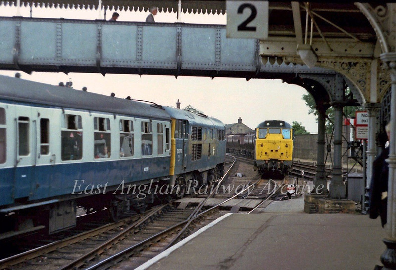 31 meets 31.  31173 stands at platform 1 at March with the 0919 Manchester Piccadilly to Yarmouth and is about to be passed by 31236 on the Rockware Glass, Middleton Towers to Doncaster sand train.  28th July 1979.