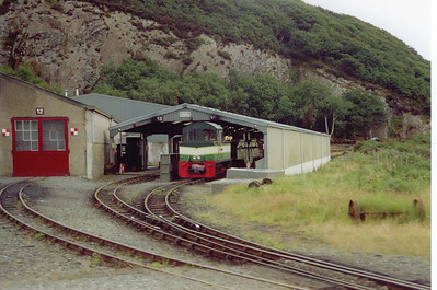 "Out on the road to Blaenau Ffestiniog and the train passes Boston Lodge works.  Parked up in the carriage shed is another of the railway's diesel locos ""Castell Criccieth/Criccieth Castle""."