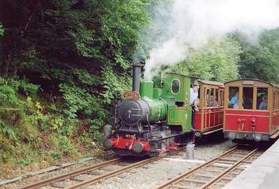 """Up and down trains pass here at Abergynolwyn and this is No 6 Douglas passing with the 1140 Tywyn to Nant Gwernol service called """"The Quarryman"""".  No 6 is an Andrew Barclay, of Kilmarnock, design of 1918 built for the Airservice Construction Corps and wirked on the RAF railway at Calshot Spit between 1921 and 1945.  After a period in store at Calshot it was bought in 1949 by Abelson & Co. (Engineers) Ltd. who presented it to the Talyllyn in 1953. After overhaul and alteration from 2ft to 2ft 3in gauge, it entered service in 1954"""
