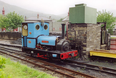 Light blue livery 0-4-0T Thomas Bach of 1904 vintage stands in the pouring rain beside the water tower at Gilfach Ddu station on a portion of the Padarn Railway that has been reopened for tourists.  The original Padarn Railway, of 4ft gauge, took the finished slate from the quarry to the standard gauge railway at Port Dinorwic.