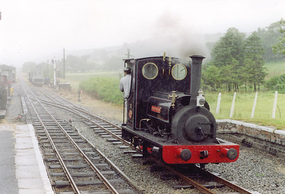 """It is pouring with rain and I'm in a foul mood after Ross and I were almost hit by a high speed car coming towards us on a narrow road.  This is the Bala Lake Railway and loco """"Maid Marion"""" runs round its train at Llanuwchllyn.  The loco is another exDinorwic Quarry Hunslet built in 1903.  The station and formation is the former standard gauge GWR line that ran from near Ruabon to Morfa Mawddach via Llangollen and Bala.  The line closed on 18/1/1965 throughout and the section between Bala and Llanuwchllyn has been reopened to narrow gauge and the part between Llangollen and Carrog  is a standard gauge railway.  This was the only photo I took this day. 2/8/2000"""