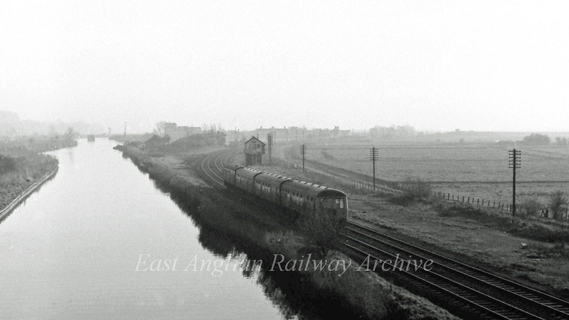 View from the A143 road bridge at Haddiscoe on 29th November 1975. The 1202 Norwich to Lowestoft is approaching the station. The Haddiscoe Yard signal box is no longer with us and I wish I'd got a close up pic while I had the opportunity. The New Cut runs to the left with the River Waveney in the distance. In the middle of the river, in the distance, can be seen the central pillar of the St Olaves Swing Bridge where the Beccles to Yarmouth South Town line once crossed at that point. On the sky line to the right of the pillar the signal box controlling the swing bridge and Haddiscoe High Level station can just be made out.