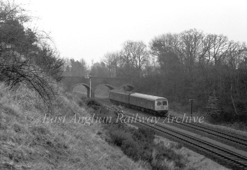 The 1115 Lowestoft to Norwich passes Oulton Broad North's distant with the adjacent Prospect Road Bridge. 10th January 1976.