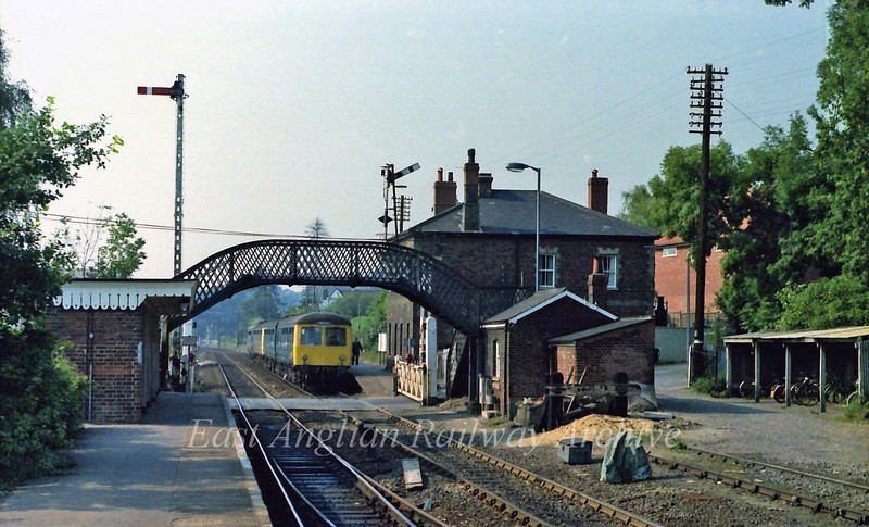 Brundall Station, junction for the Yarmouth line via Lingwood and Acle on 6th September 1979. The 1500 Norwich to Lowestoft stands in the platform. The two platforms are split at the level crossing.