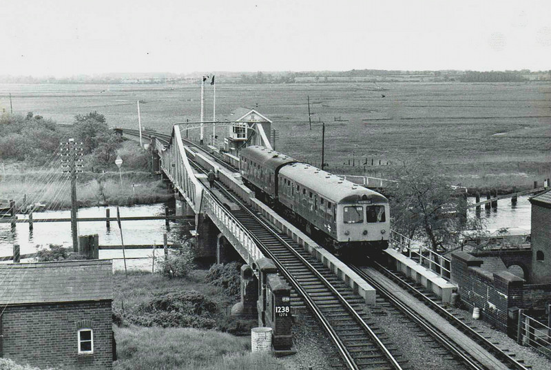 0937 Lowestoft to Norwich crosses the River Yare at Reedham Swing Bridge with typical broadland scenary as a backdrop. 17th May 1977