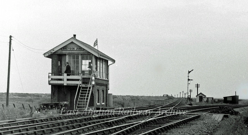 Breydon Junction near Great Yarmouth on 25th June 1977.  The line to the left is the single line to Reedham via Berney Arms, that to the right to Brundall. The flag on the box is presumedly for the queens silver? jubilee in 1977. The box has now been demolished.
