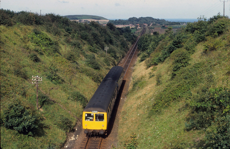 "A Cravens two car unit between  West Runton and Sheringham. September 1981. "" You CAN see the sea, it's over there between the land and the sky"" With apologies to Basil Fawlty."