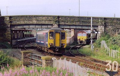 Class 156 sprinter 156441 departs Workington with 2C37 0650 Barrow in Furness to Carlisle class 2 service.  In the station is 66013 waiting for the road to go to the docks.