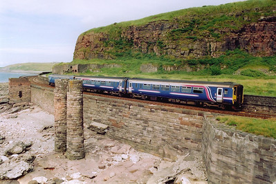 156420 and 153324 come by Redness Point heading for Lancaster with 2C42 1420 off Carlisle.  I have no idea what the two pillars on the foreshore were actually for.  A short tunnel still passes below the railway from the building on the left to the path below the cliff.