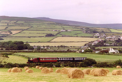 Rolled bailed hay forms the foreground for No 10 and its three coach 1435 Douglas to Port Erin train seen on the approach to Port St Mary.