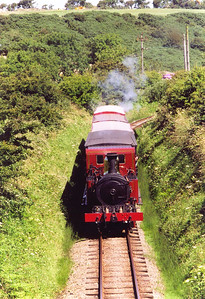 No 12 is working back to Port Erin from Douglas, 1200 off, seen near Ballacostain. Note the difference in roof styles for the four coaches on the drawbar.
