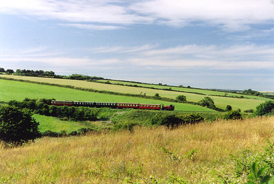 No 10 is seen again just south of Santon but heading back to Douglas now, 1635 from Port Erin. The 5 coach train passes over quite a tall embankment and is bathed in sunshine with a blue sky and whisps of white cloud overhead.  24/7/2001