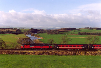 Due to engineering work on the WCML between Preston and Carlisle, trains were diverted over the Settle and Carlisle Railway. Snow on the hills in the distance with the River Eamont running through the centre of the photo as 47789 passes with 1O38 0738 Glasgow Central to Bournemouth cross country service.