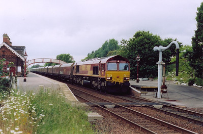 I was advised about this train by the station staff. 66130 wheels a loaded coal train south through the station with the working former Midland Railway water crane to the left. The working is not identified.