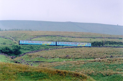 156468 passes the up starter at Garsdale after its station stop. The working is 2H93 1426 from Carlisle to Leeds. In steam days there were water troughs here, the highest in the country.