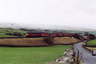 "Further to the south the railway is at a lower level and below a very well defined snow line. 47732 climbs hard against the 1 in 100 pull of ""The Long Drag"" just to the north of Horton in Ribblesdale. The train is a VXC working, 1S49 1042 Birmingham International to Edinburgh cross country."