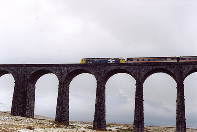 BR blue large logo 47847 crosses the lofty arches of Ribblehead Viduct some 40 minutes late with 1M33 1350 Edinburgh to Birmingham New Street.
