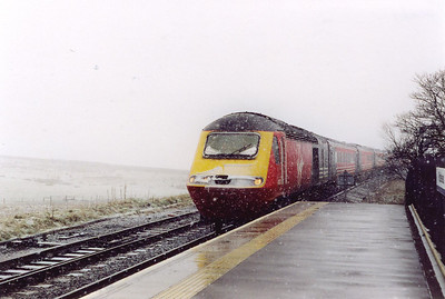 "Moving on to Ribblehead was only possible by driving via Hawes as the Coal Road was impassable. 43103 leads the southbound ""Cornish Scot"" 1V52 0910 Edinburgh to Penzance cross country long distance working through the wet platforms of Ribblehead. The snow is yet to lie on the wet platforms."