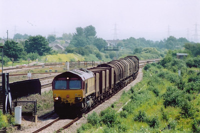 The Down Relief Road gets a bit of use as 66118 slowly runs round the back of the station with a train made up of empty FCA, BYA, JSA steel carriers.  The train is 6V05 0939 Round Oak to Margam empty steel.