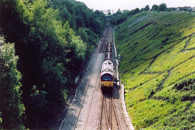 Moving east to Chipping Sodbury now and an overbridge looking down into a deep cutting.  67022 approaches and clatters over the pointwork for the west end of the up goods loop and crossover with four empty flats in tow.  The working is 6M33 1622 Avonmouth to Wembley Enterprise.