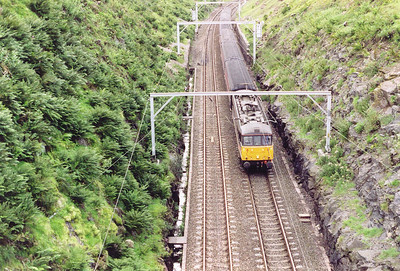 To the south of the summit the cutting gets deeper and is spanned by a high footbridge. Looking down from the brdige, an unknown class 86 passes below the a cross country working from Glasgow Central to Birmingham New Street, 1608 off 1M44.