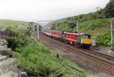 The actual summit at Shap lies in a cutting at 916 feet above sea level and the line is level for just under a mile. 86244 heads south and is at the top of the drop to Tebay with 1M33 1440 Edinburgh to Birmingham New Street.