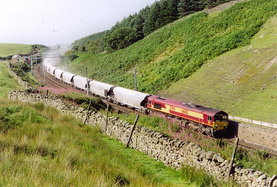 A move to the actual summit at Shap and the first train I see is 66180 now heading south with its train of covered limestone. As it speeds by a trail of dust fills the cutting. The train is 6V23 1618 MWFO Hardendale to Margam lime train. The lime is used in the steel making process.