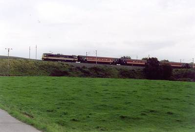 When the late Ivo Peters came to photograph in the area he stayed at the Shap Wells Hotel. 87012 passes the access road to the hotel as it propels its train down the bank. The working is 1M34 1700 Glasgow Central to Euston. Whilst parked here, my car was attacked by a cow who stuck her head in the drivers side window and slobbered all over the steering wheel!!!  Yuck!!