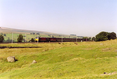 Scout Green is a famous location for photography on Shap Bank. The former block post signalbox stood beside a minor road level crossing behind the trees to the right. 86212 comes by with 1O38 0910 Edinburgh to Bournemouth. Motive power will be swapped at Preston for a class 47.
