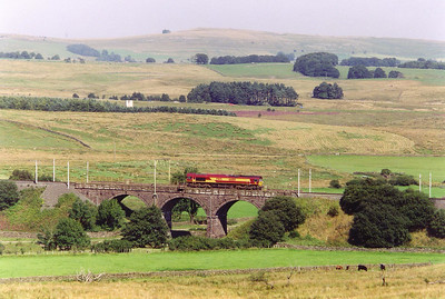 This shot was taken during another location move. 66180 runs north crossing Birkbeck Viaduct over the Birk Beck. Its duty is 0V23 1342 MWFO Carnforth to Hardendale Quarry.
