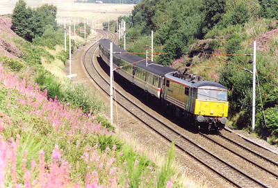 A southbound cross country working passes Greenholme behind Virgin liveried 86248 hauling a rake of InterCity mkII coaches on 1O40 1040 Edinburgh to Brighton via Manchester. The electric loco will come off at Preston to be replaced by a class 47.
